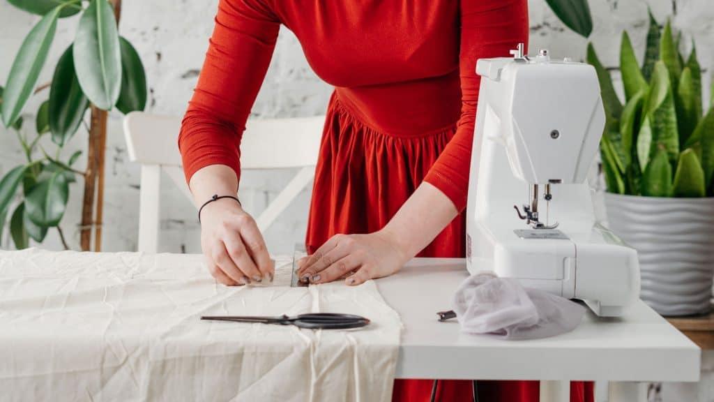 femme qui découpe son tissu pour coudre un masque en tissus contre le coronavirus