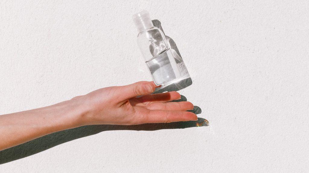 mains d'une femme qui tient une bouteille de gel hydroalcoolique
